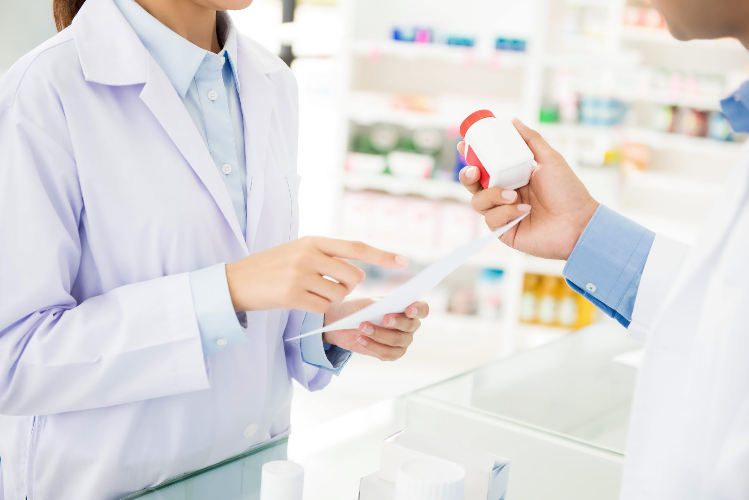 Pharmacists holding medicine bottle and discussing prescription drug in a pharmacy or drugstore